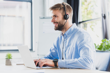 side view of smiling young call center operator in headset using laptop in office