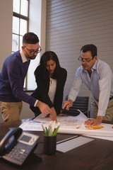 Business colleagues discussing over blueprint in meeting room
