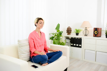 young woman at home practicing yoga and meditation with smartphone application Fototapete