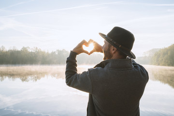 Young man standing by the lake at sunrise making a heart shape finger frame on the beautiful landscape, reflection on water. People love travel