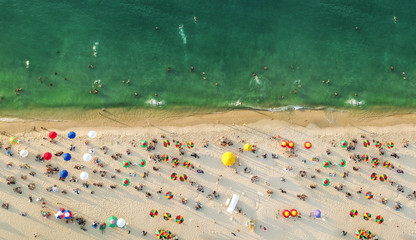 Aerial view of a beach with colorful umbrellas, people swimming in the sea, sunny day. Drone landscape from above