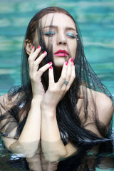 Fashion photo of woman wrapped in black sheer fabric in swimming pool