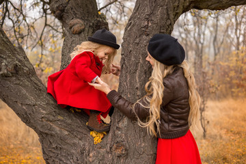girl in a red coat climbed up an old tree and her mother supports