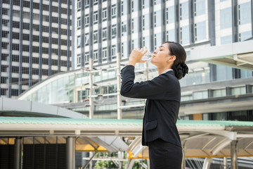 Asian business woman standing and drinking pure mineral water from plastic bottle in hot summer day with background of building.