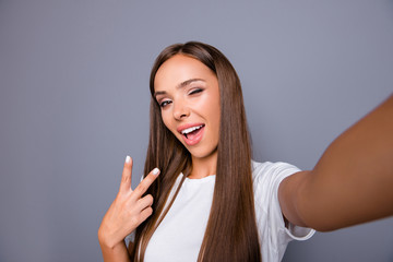 Self-portrait of brown-haired gorgeous attractive nice smiling young lady over grey background, showing v-sign gesture, opened mouth, winking, blinking, flirting, self photographing, isolated