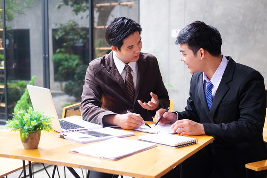 Photo of two colleagues businessman discussing about the project.