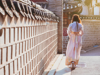 travel and tourist korea concept from backside long hair woman in korea traditional cloth (hanbok) walk in vintage town and old brick wall with soft focus background