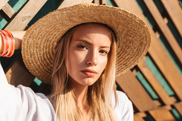 Portrait of attractive young blond woman 20s in straw hat and swimwear posing against wooden beams, on sunny summer day