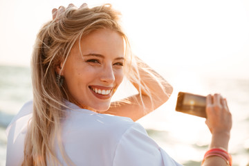 Photo of joyous blonde woman 20s smiling, and taking photo of sunrise above sea, while walking on summer beach