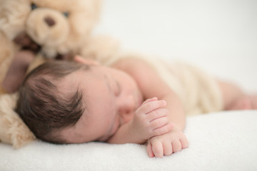 Cute newborn baby sleeps on a blanket with a toy teddy bear - happy family moments