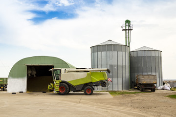 combine and truck near a granary and silos