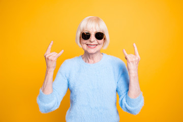 Modern old lady hold hands up and showing sign rock and roll iso