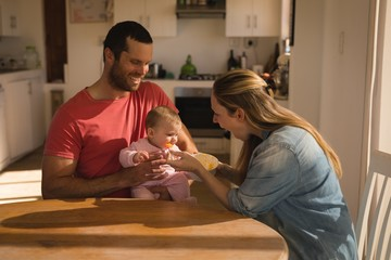Parents feeding their baby boy at home