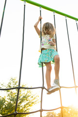 Girl playing on rope climbing apparatus