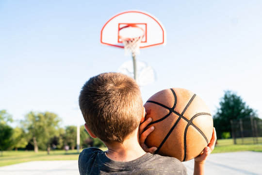 Boy throwing basketball with two hands