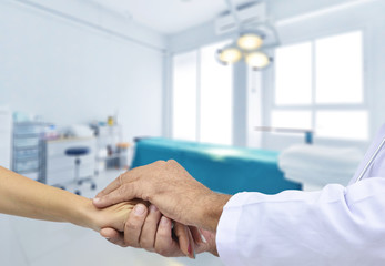 Friendly male doctor's hands holding female hand for encouragement and empathy. Trust cheering and support ,medical ethics concept. operating room background