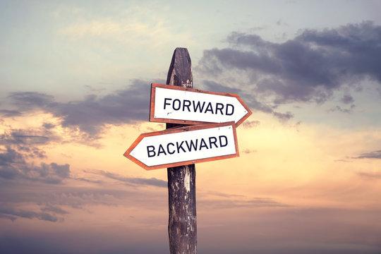 Forward, backward - wooden signpost on sunset background.
