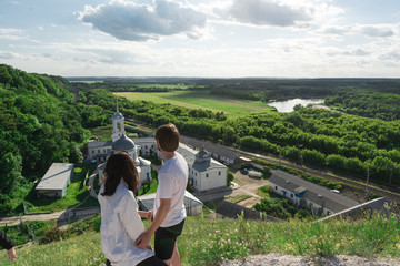 young couple travels standing on a hill and admiring the magnificent views of the valley, river and monastery