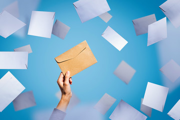 A female hand holds an envelope on a background of falling white envelopes
