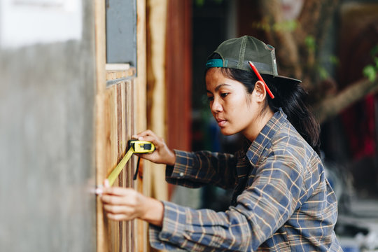 young woman using measuring tape and marking the wall