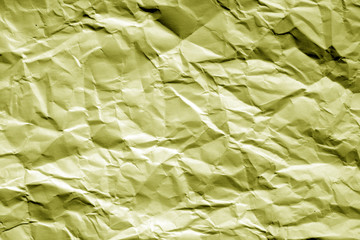 Crumpled sheet of paper in yellow tone.