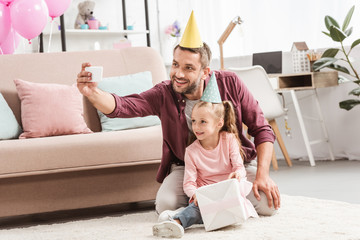 smiling father and daughter in party hats taking selfie with gift for birthday
