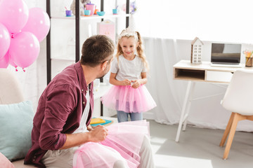 father looking to daughter in pink tutu skirt