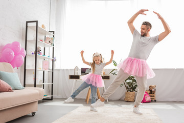 funny father and daughter in pink tutu skirts dancing like ballerinas