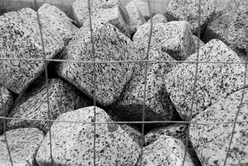 Close-up of pile of granite pieces into a metal net
