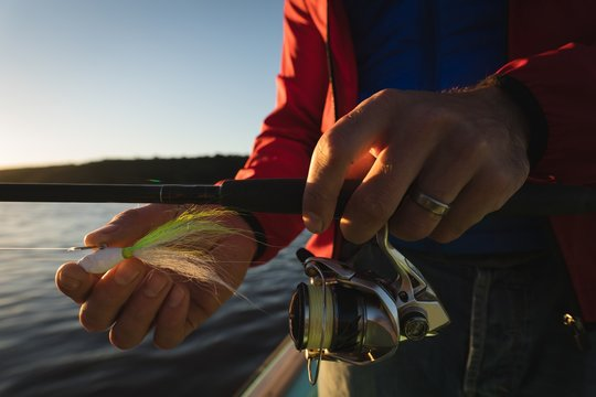 Man tying bait in fishing rod on motorboat