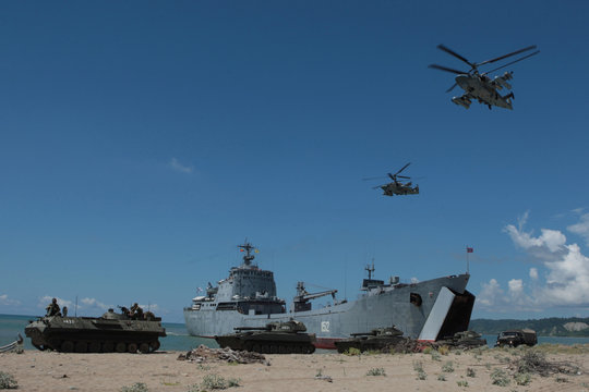 Military Ka-52 helicopters fly over the large landing ship Nikolay Filchenkov deploying armoured vehicles during military exercises of Russian armed forces in Georgia's breakaway region of Abkhazia