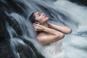Beautiful woman model posing under waterfall wearing white swimwear