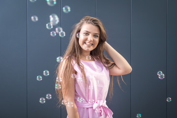 Teenage girl and soap bubbles against gray wall