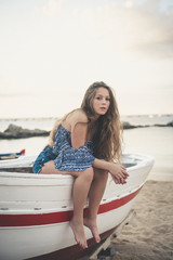 Portrait of teenage girl sitting on boat at beach against cloudy sky during sunset