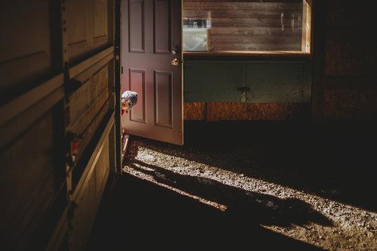 Portrait of baby boy peeking through doorway in abandoned house