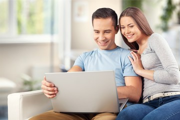 Young business couple using laptop at home,