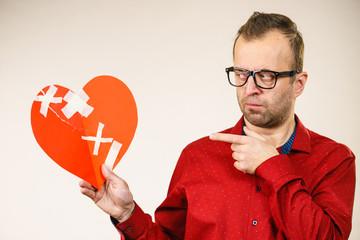 Thinking adult man holding broken heart