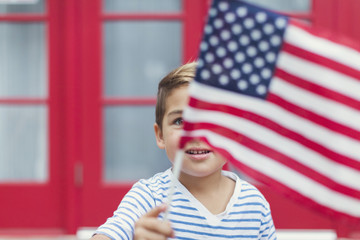 Close-up of boy waving American flag while standing against house