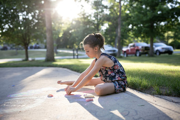 Side view of girl drawing with chalks on footpath in yard