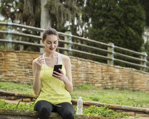 Low angle view of woman using smart phone while sitting at park