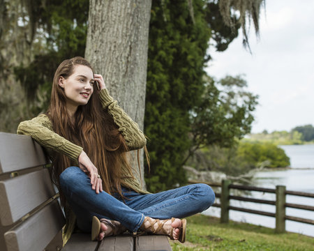Young smiling woman sitting on bench in park