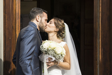 Newlywed couple kissing while standing at church entrance