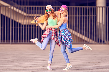 Wall Mural - Two Girl Having Fun with Skateboard. Outdoor, Urban background. Playful redhead Hipster Friend Enjoy Sunny day, Happy Smiling. Young Beautiful Model Woman in Fashion Trendy Outfit.