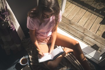 High angle view of young woman writing in diary by window