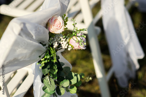Close up of chairs with floral decor for outdoor wedding ceremony