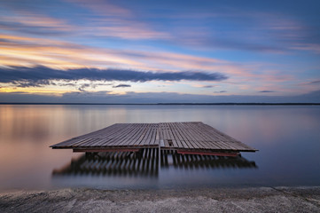 Wooden raft on calm lake against sky during sunset