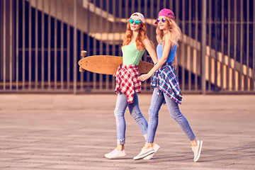 Wall Mural - Full-length shot two female Skaters best friends Jump. Playful Girl Enjoy Outdoor Urban. Young Beautiful european Woman in Fashion Trendy Sunglasses