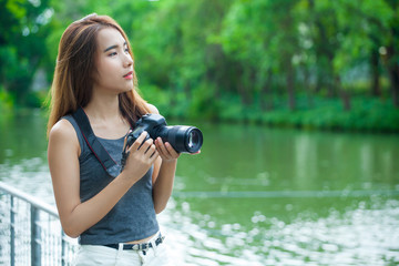 Young Asian woman photographer. beautiful girl with camera at summer green park taking pictures outdoors