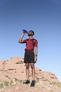 Male hiker drinking water while standing on rock against blue sky