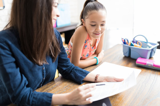 Girl Reading Notes Held By Teacher At Table In House